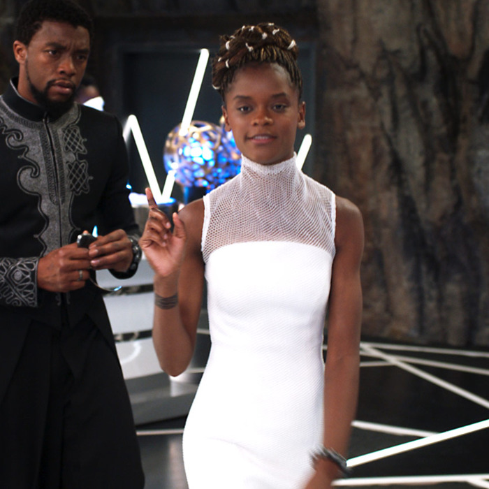 Shuri in a white dress showing T'Challa how brilliant she is.
