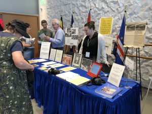 The PCCA exhibit features several posters on easels behind a blue table with seven more documents, two binders, and an IPad. A woman stands in front of the exhibit. Robert Newlen and Leslie Nellis stand behind the exhibit to answer questions.