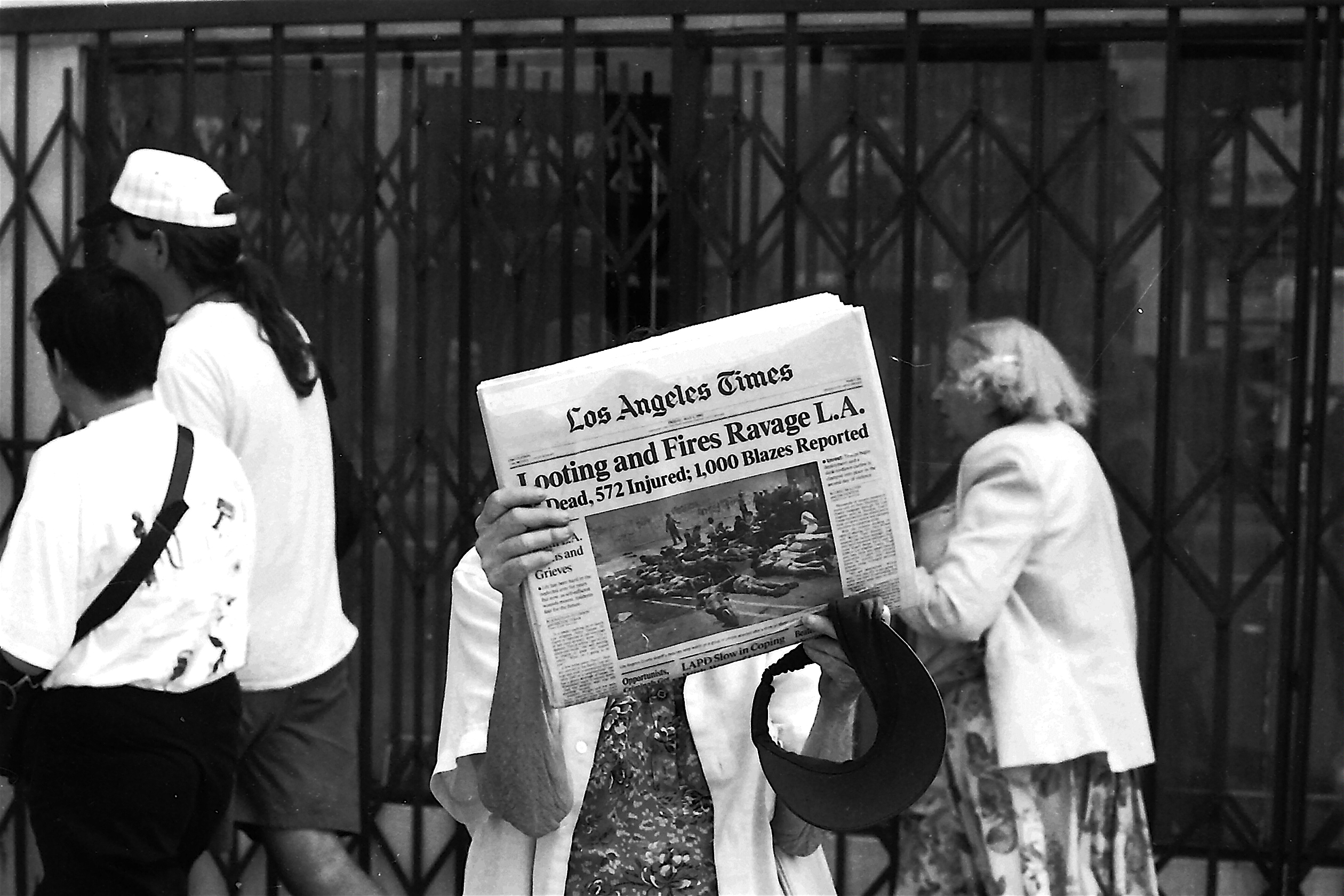 "Woman holds newspaper up to show headline, ""looting and fires ravage L.A."""