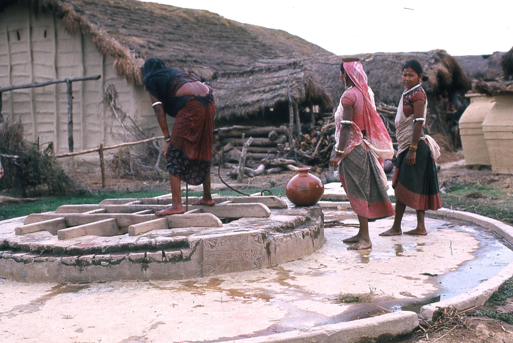 Three women collect water in pots from village well. One woman looks down the well and another faces the camera.