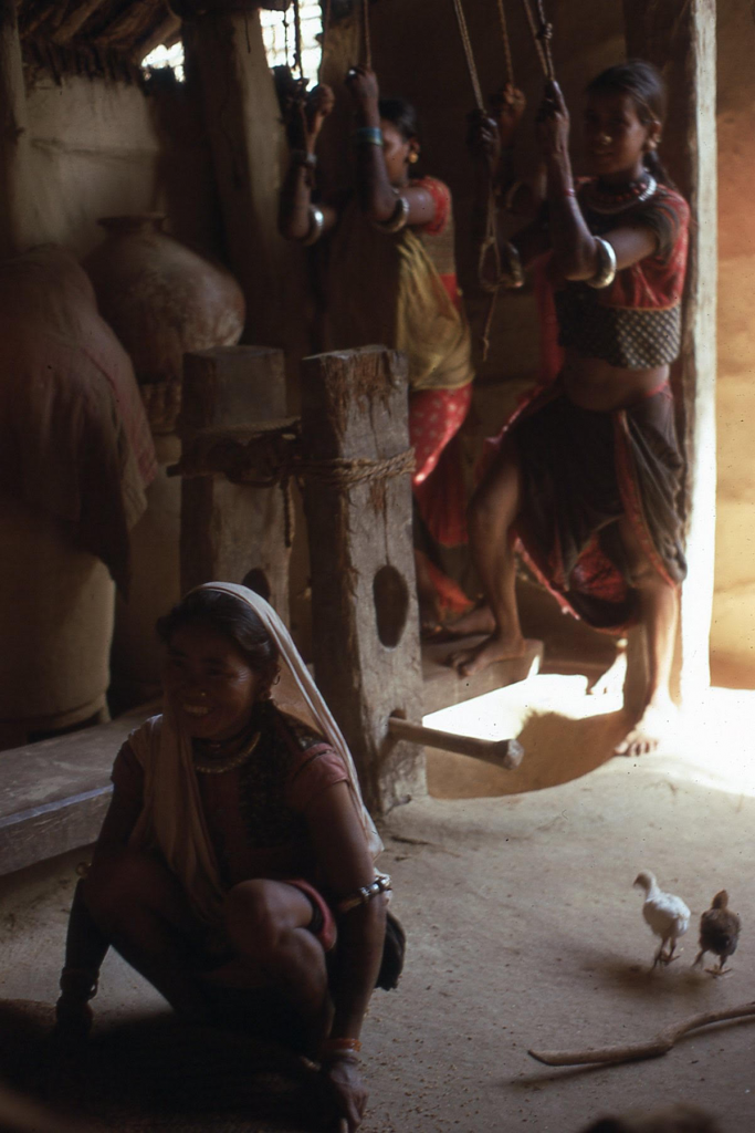 Three women husk rice inside of a building. Two women pull on rope over their heads as another crouches in the foreground.