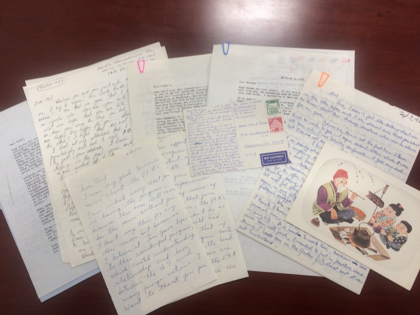 Various letters, postcards, and airmail scattered on a table.