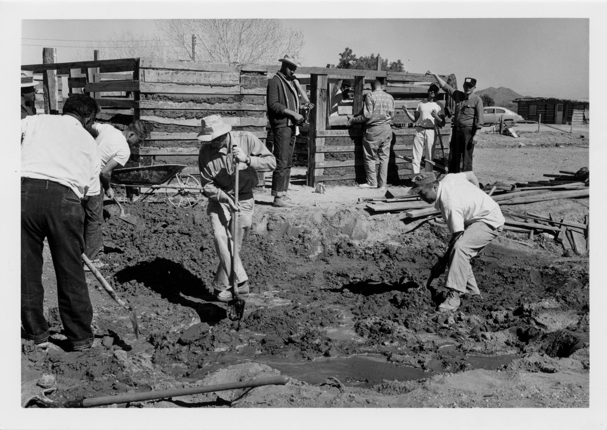 Black and white photo of three men dig in dirt with shovels. Another group of men stand along a wooden fence in the background.