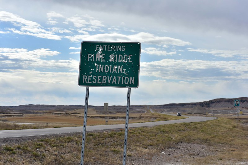 Landscape color photo of the Pine Ridge road sign, covered in bullet holes.